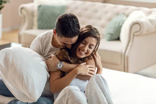 jonge gelukkige paar in de liefde te omhelzen in de slaapkamer. - verliefd worden stockfoto's en -beelden