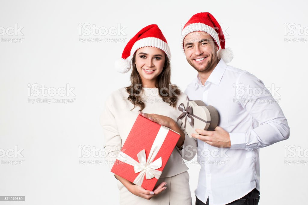 Young happy couple in Santa hat with gift boxes. Concept Christmas,...