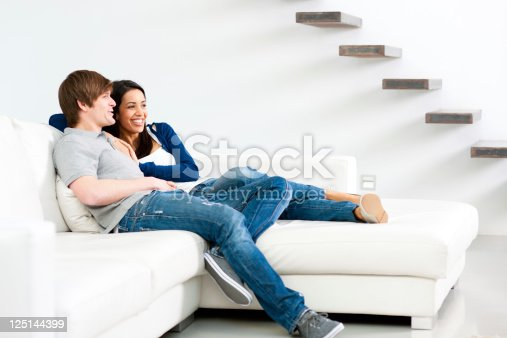Young happy couple making plans in modern living room