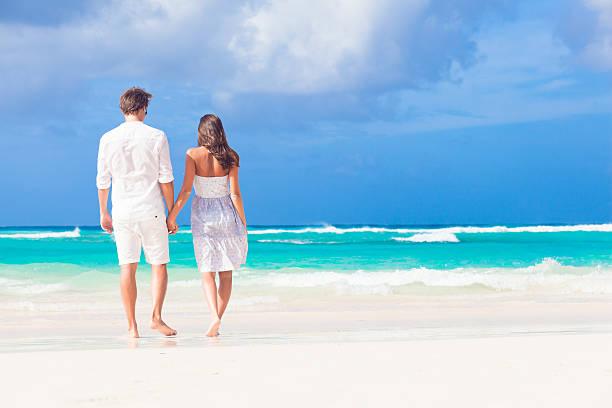 giovane coppia felice sulla spiaggia. tropicale in bianco luna di miele - attività romantica foto e immagini stock
