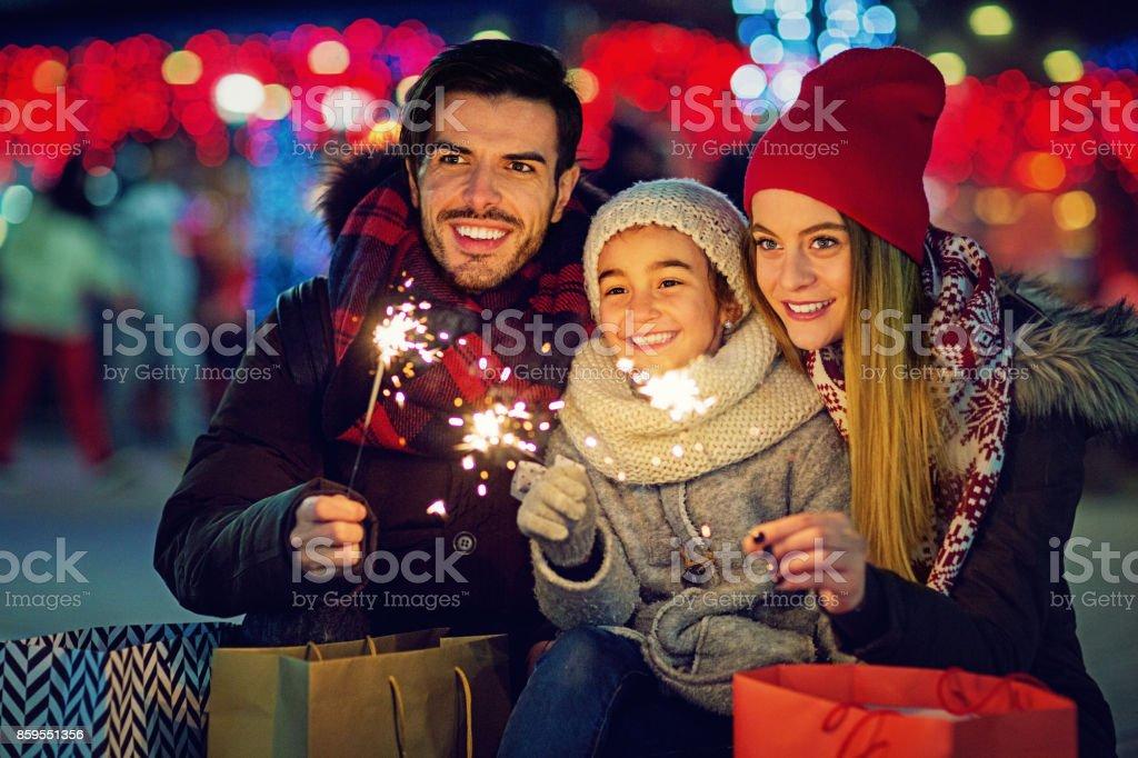Genç, mutlu çift, kızları sarılma ve Noel'de havai fişek holding stok fotoğrafı