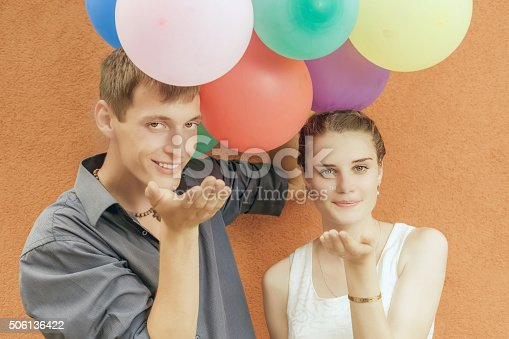 istock Young happy couple kissing and holding balloons 506136422