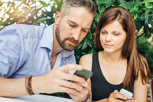 young happy couple looking at mobile phone - kvinna cloes up bildbanksfoton och bilder