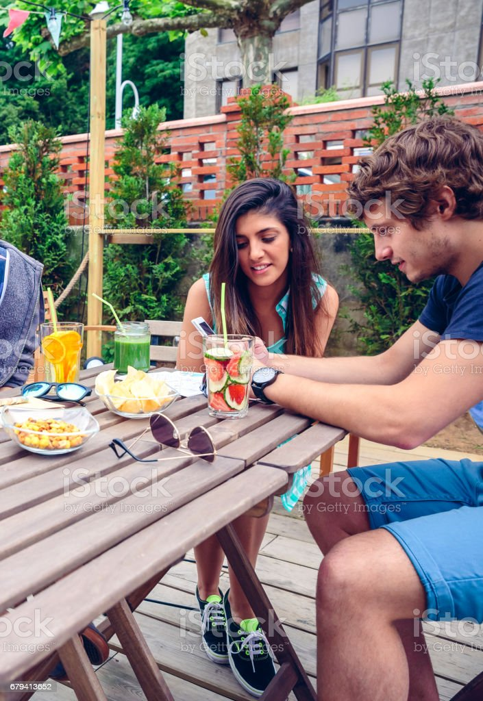 Young happy couple looking smartphone outdoors in summer royalty-free stock photo