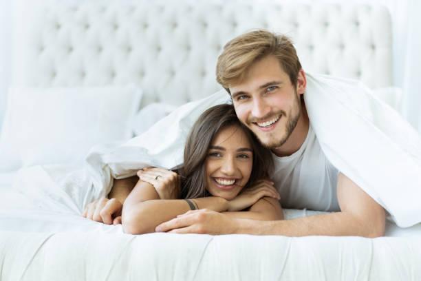 Junges glückliches Paar liegt zusammen im Bett. – Foto