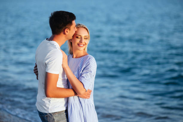 Young happy couple on beach at summer vacation stock photo