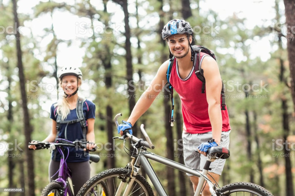 Young happy couple on bikes looking at camera foto stock royalty-free