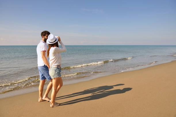 Young happy couple on seashore. Male has beard. stock photo