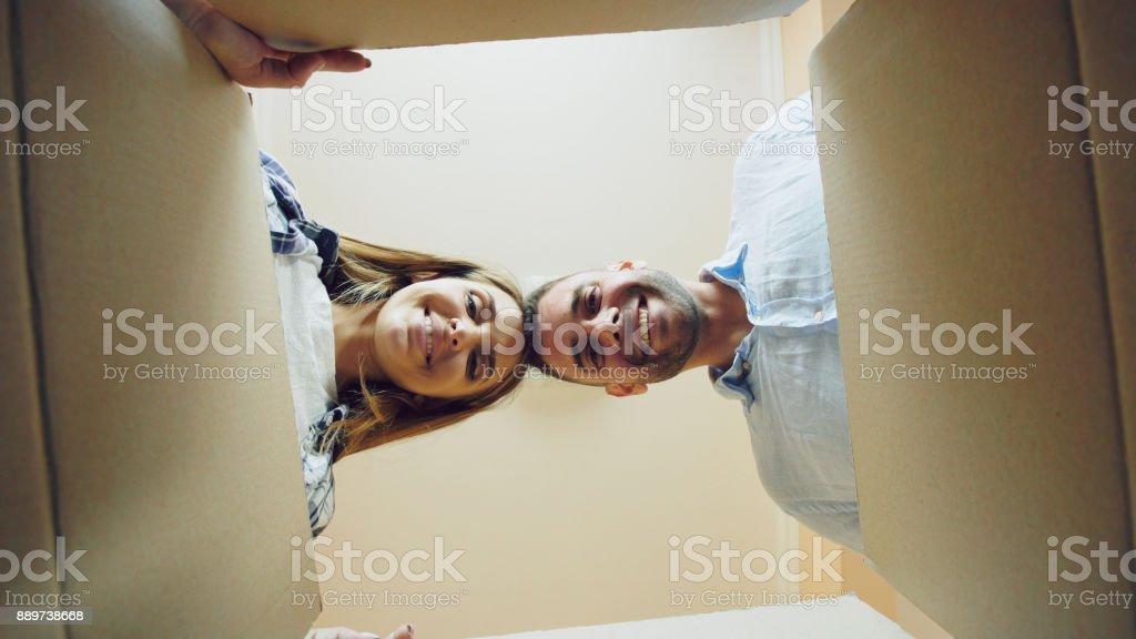 Young happy couple opening cardboard box after relocation and looking inside in new house stock photo
