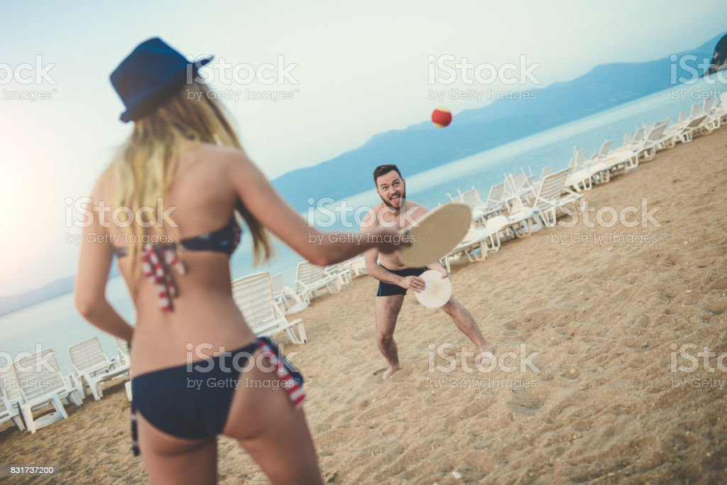 Young Happy Couple Play Beach Tennis Paddle Ball - foto stock