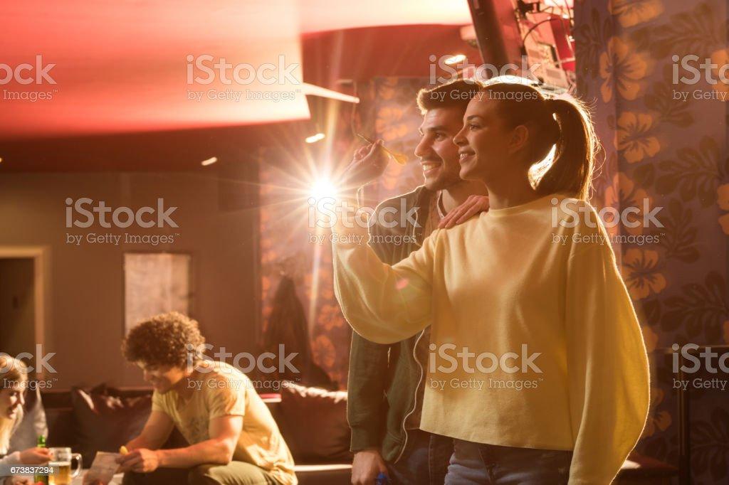 Oynayan genç mutlu çift eğlence kulübünde Dart. royalty-free stock photo