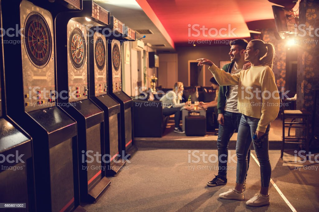 Young happy couple playing darts in entertainment club. stock photo