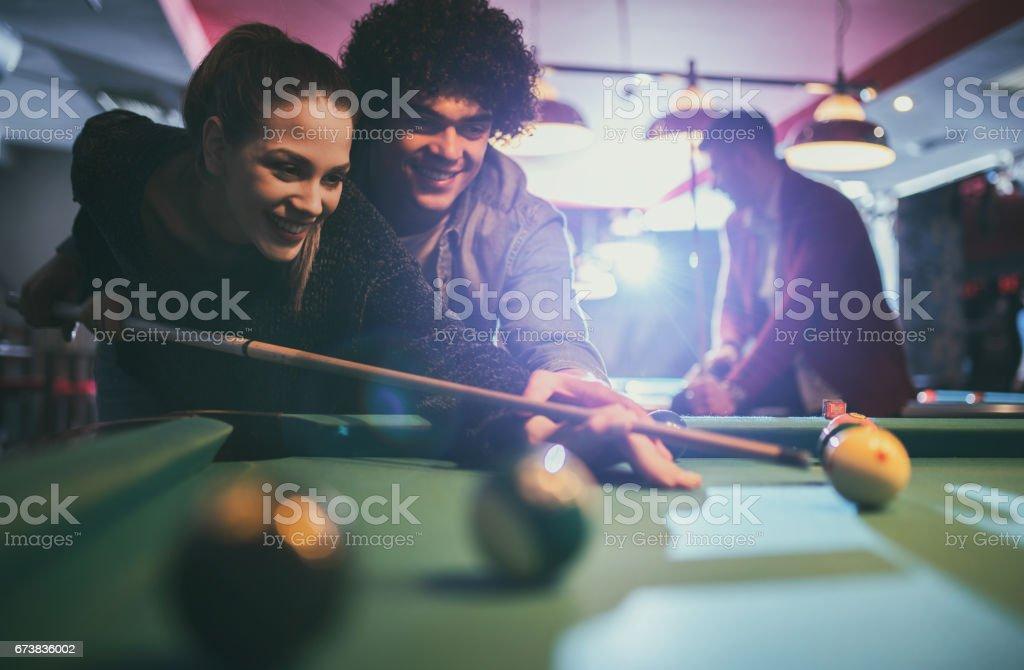 Jeune couple heureux de jouer snooker dans une salle de billard. photo libre de droits