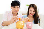 istock Young happy couple putting coin into piggy bank 803077388