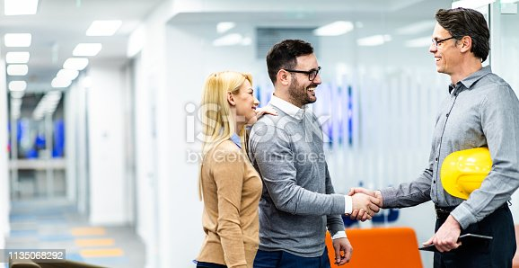 istock Young happy couple reached an agreement with an architect in the office. 1135068292