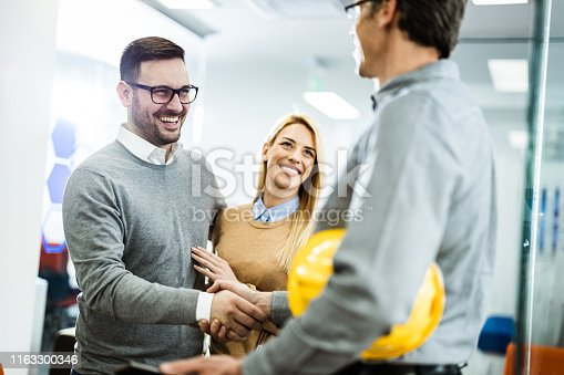 istock Young happy couple reached an agreement with an architect in the office. 1163300346