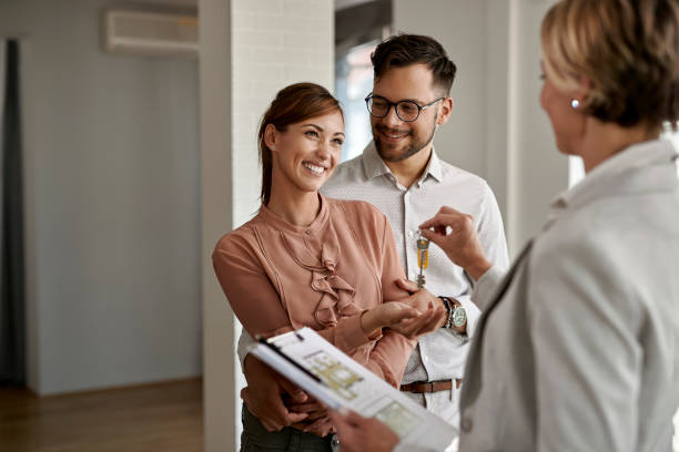 Young happy couple receiving keys of their new home from real estate agent. stock photo
