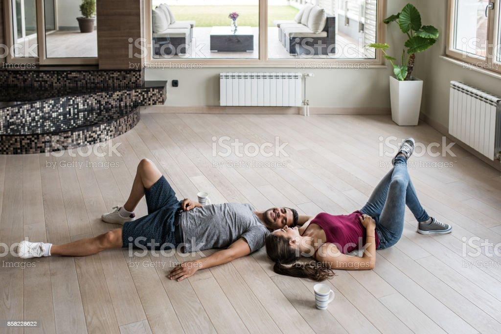 Junge glückliche paar entspannende auf einem Parkettboden in ihrer neuen Wohnung. - Lizenzfrei Anfang Stock-Foto