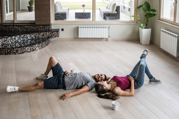 Young happy couple relaxing on a parquet floor at their new apartment. stock photo
