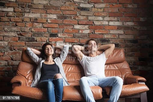 1143763067istockphoto Young happy couple relaxing on comfortable leather couch at home 917874768