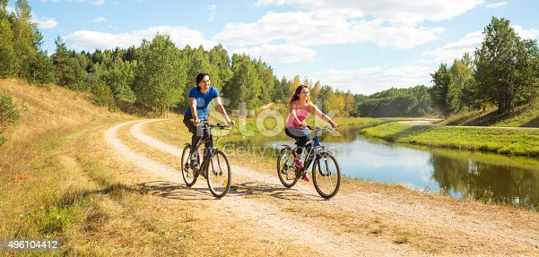 969439086istockphoto Young Happy Couple Riding Bicycles by the River 496104412