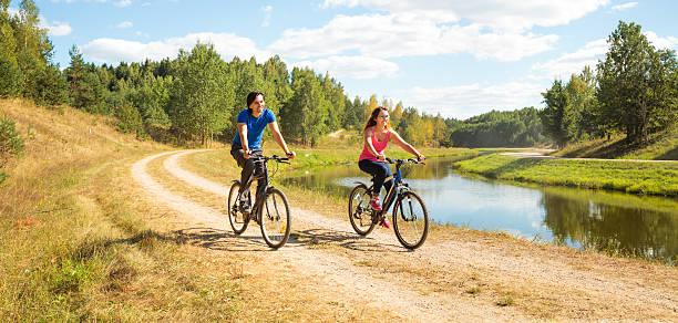Junge glückliche Paar Reiten Fahrräder durch den Fluss – Foto