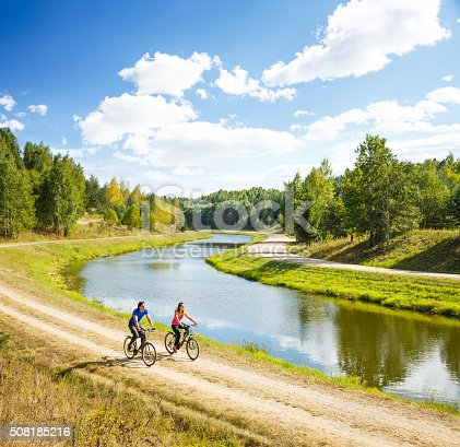 969439086 istock photo Young Happy Couple Riding Bicycles by the River 508185216