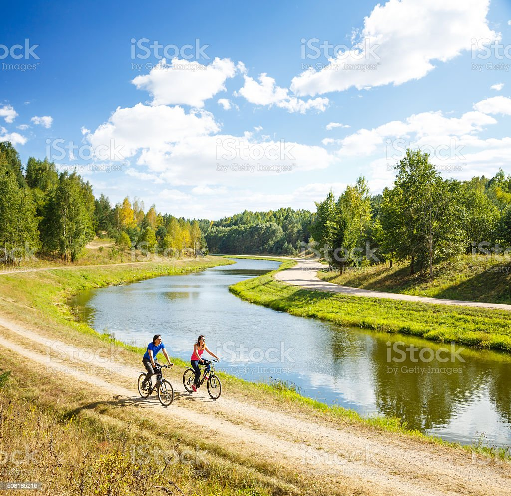 Young Happy Couple Riding Bicycles by the River stock photo