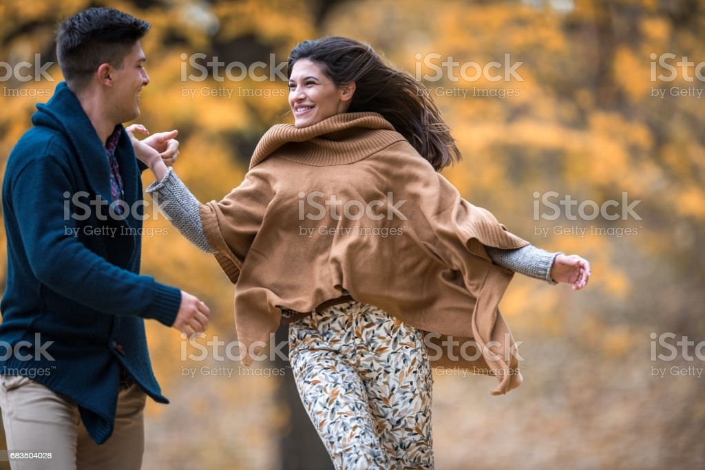 Young happy couple running and having fun in the park. stock photo