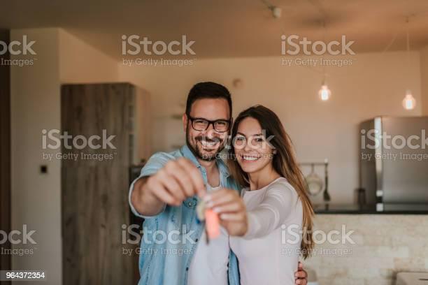 Foto de Jovem Casal Feliz Mostrando As Chaves Da Nova Casa Olhando Para A Câmera e mais fotos de stock de Adulto