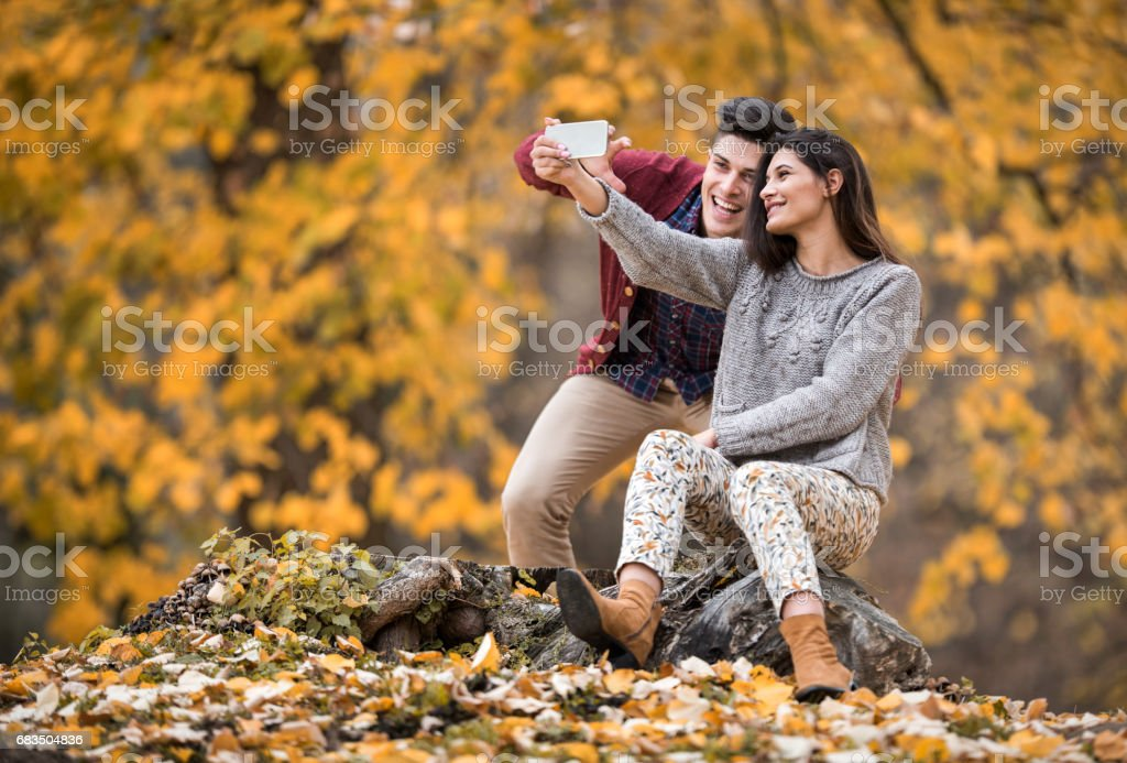 Young happy couple taking a selfie with cell phone in autumn park. stock photo