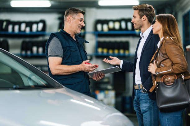 Young happy couple talking to car mechanic in auto repair shop. Happy auto repairman communicating with young couple in a workshop. auto mechanic stock pictures, royalty-free photos & images