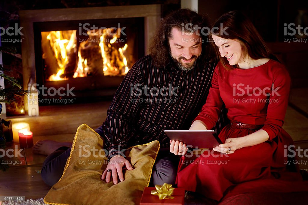 Young happy couple using tablet by fireplace in cozy room stock photo