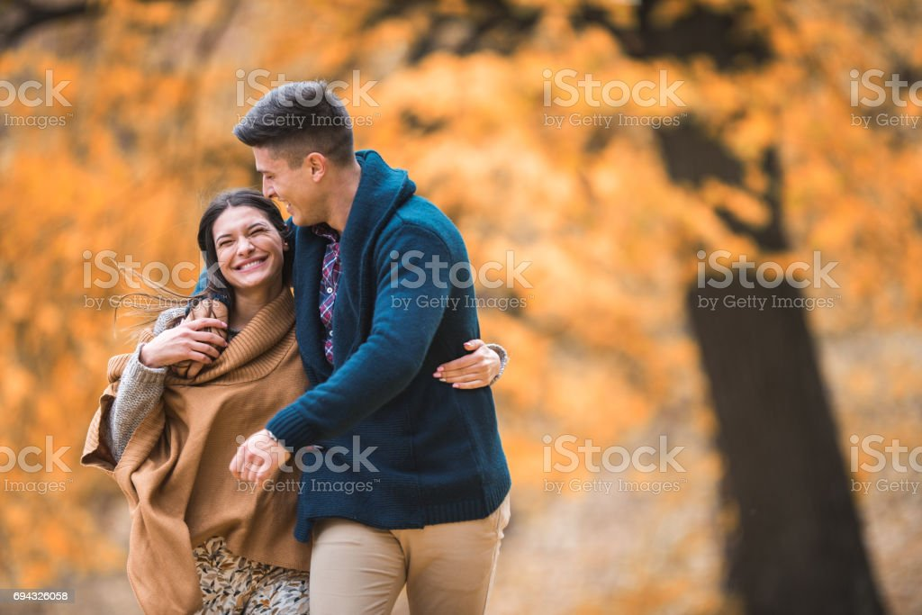 Young happy couple walking embraced in autumn park. stock photo