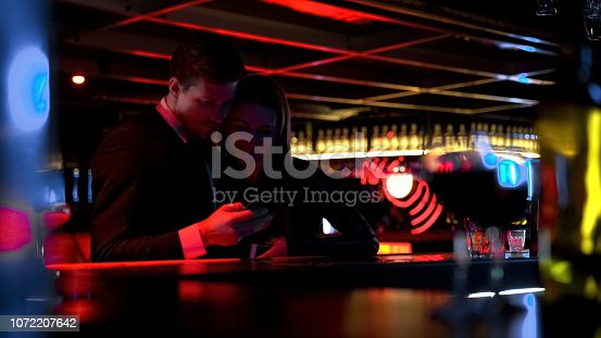 istock Young happy couple watching pictures on phone in bar, having fun together 1072207642