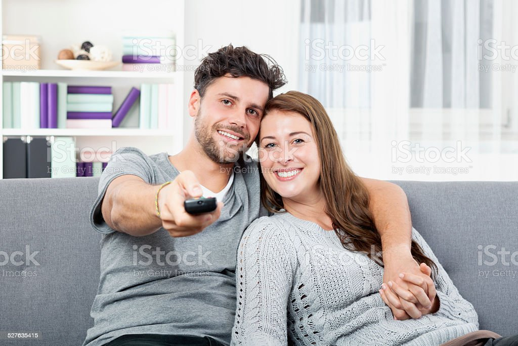 Young happy couple watching TV holding remote control stock photo