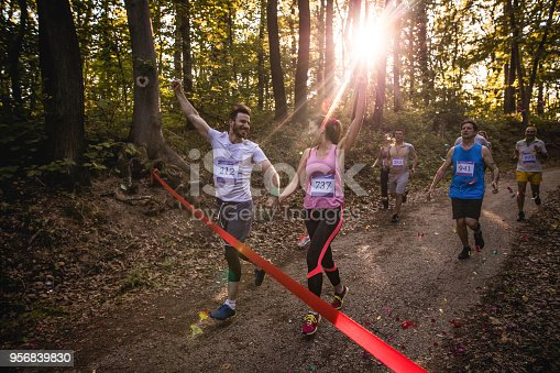 istock Young happy couple winning marathon race in the forest while crossing finish line together. 956839830