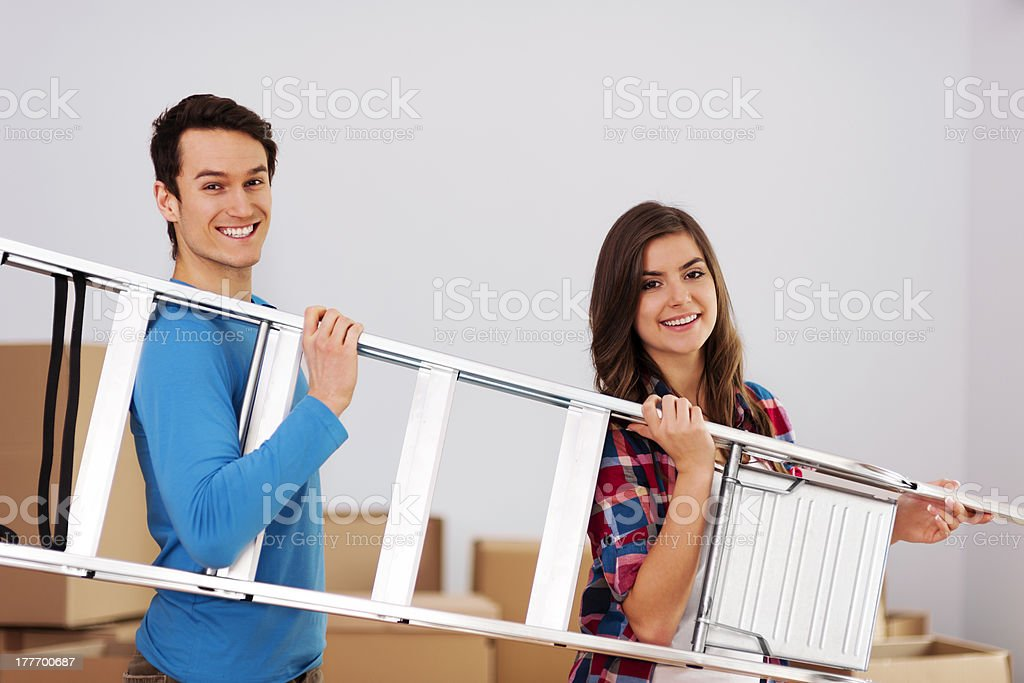 Young happy couple with a ladder royalty-free stock photo