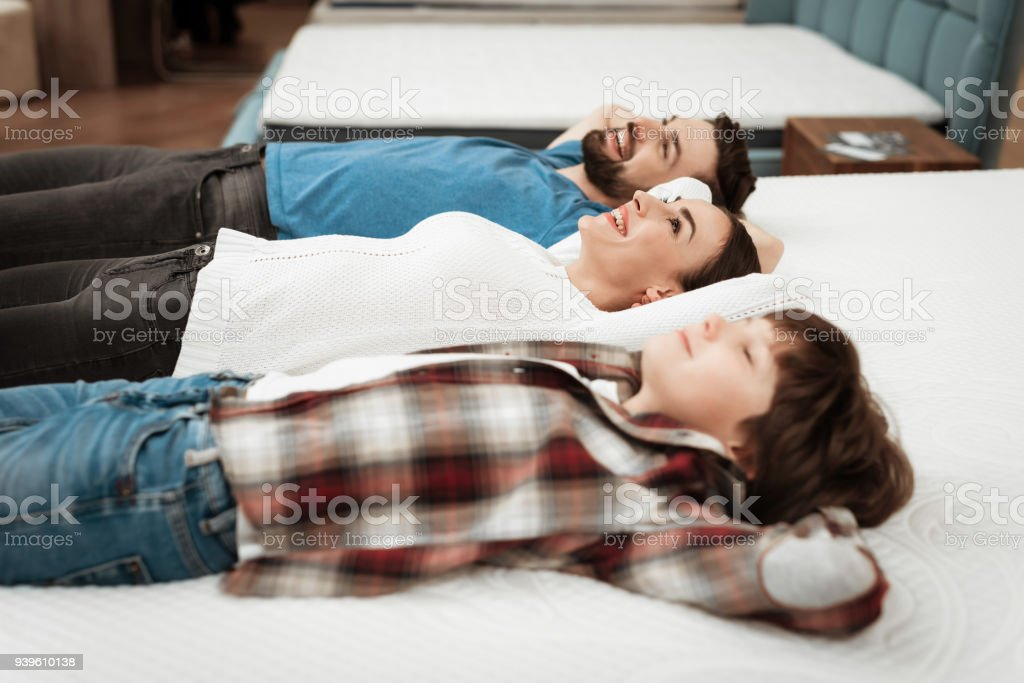 Young happy couple with cute little boy lies on bed in mattress...