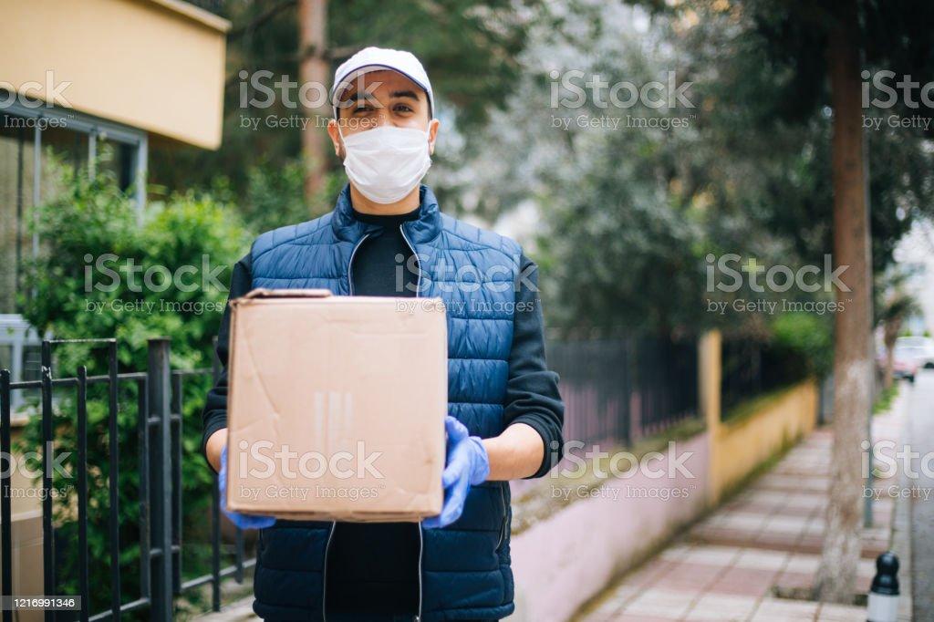 카메라를 보고 보호 마스크를 가진 젊은 행복 배달 남자 - 로열티 프리 COVID-19 스톡 사진