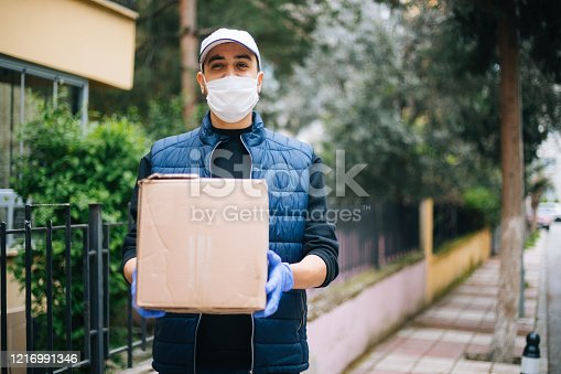 Young happy delivery man with protective mask looking at camera