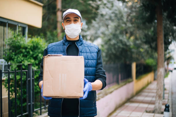 young happy delivery man with protective mask looking at camera - essential workers stock pictures, royalty-free photos & images