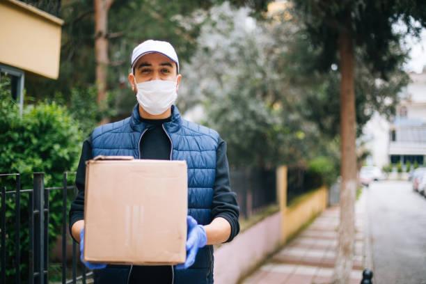카메라를 보고 보호 마스크를 가진 젊은 행복 배달 남자 스톡 사진