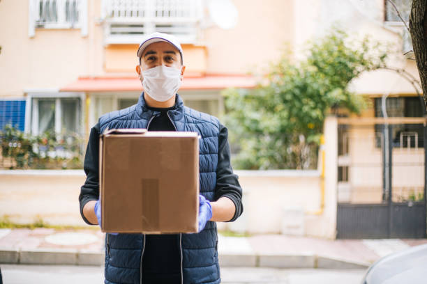 young happy delivery man with protective mask looking at camera - servizi essenziali foto e immagini stock