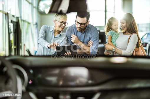 Happy family and car salesperson using touchpad in a showroom. The view is through windshield.