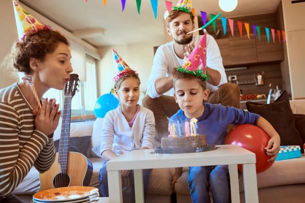 junge familie feiern geburtstag zu hause - gitarren geburtstagstorten stock-fotos und bilder