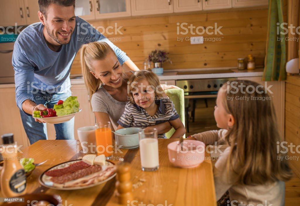 Young happy family communicating during breakfast time at home. royalty-free stock photo