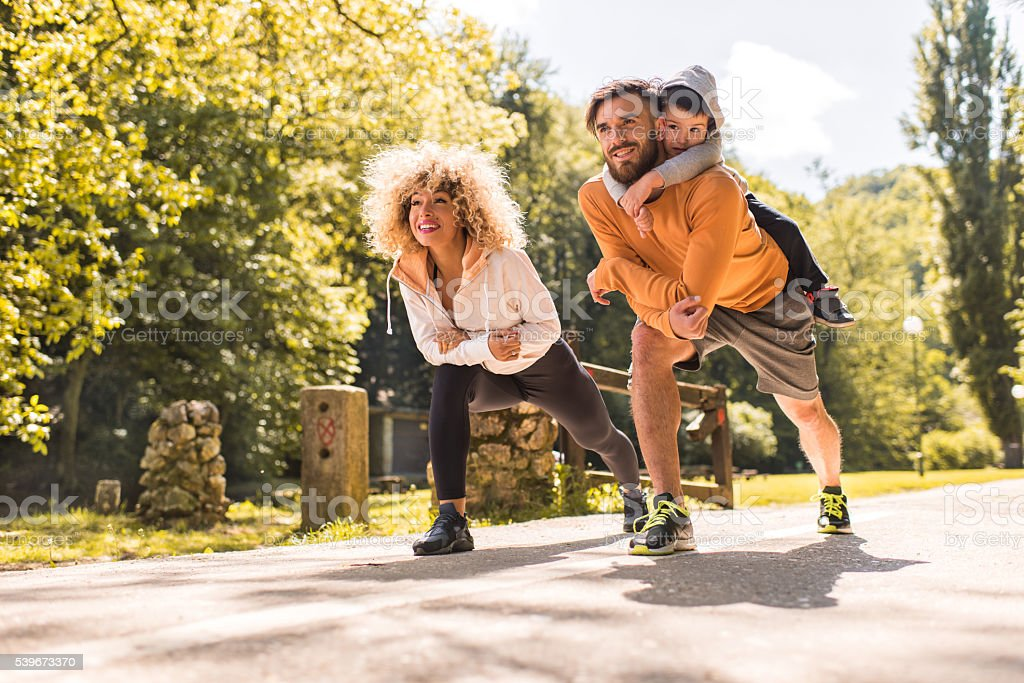 Young happy family doing stretching exercises in the park. stock photo
