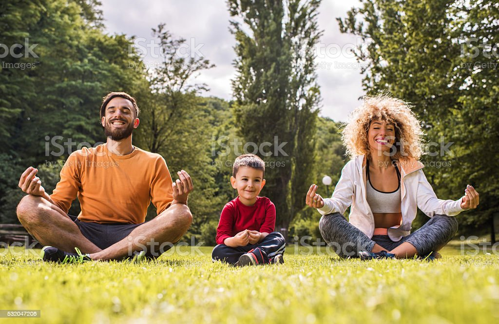 Young happy family doing Yoga relaxation exercises on a grass. stock photo