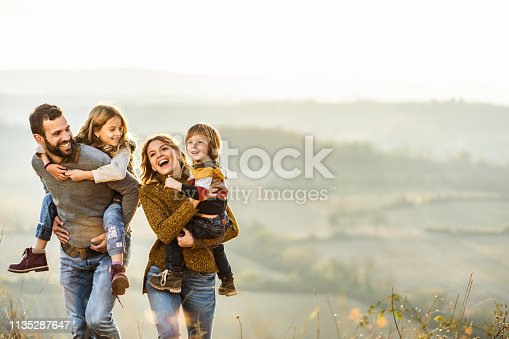 Happy parents and their small kids taking an autumn walk on the field. Father is piggybacking daughter. Copy space.